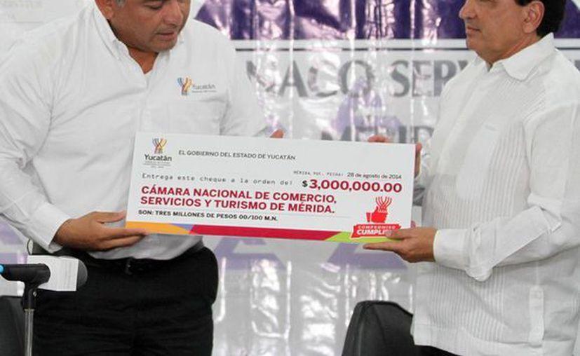 El secretario de Gobierno, Víctor Caballero, entrega un cheque por 3 mdp a José Manuel López Campos para financiar la campaña de 'Ven al centro y gana'. (Milenio Novedades)