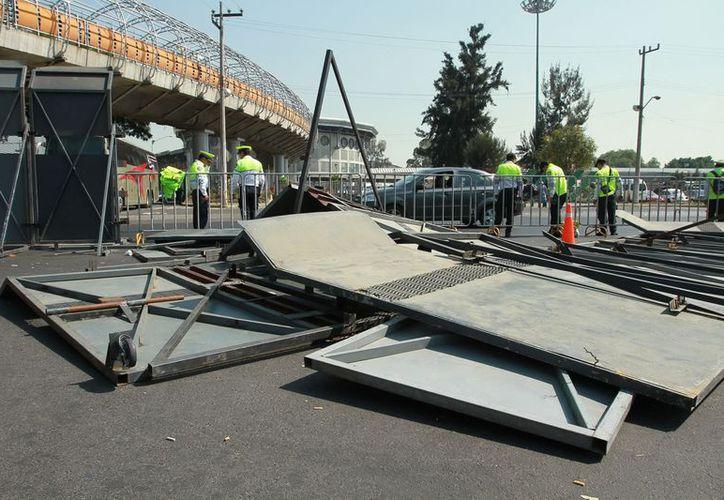 Algunos manifestantes, entre ellos funcionarios del PRD, derribaron algunas vallas en la zona aledaña a San Lázaro. (Notimex)
