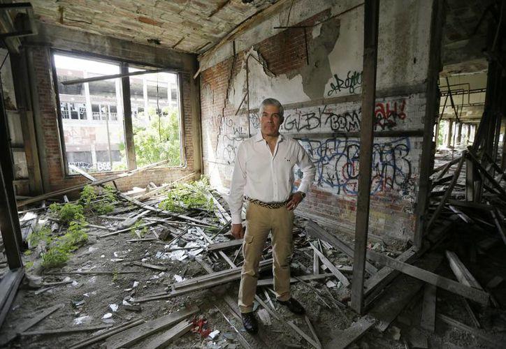 El dueño del terreno donde se ubicaba la planta Packard, el peruano Fernando Palazuelo, posa en el lugar donde proyecta tener su oficina en el terreno, en Detroit, Michigan. (AP)