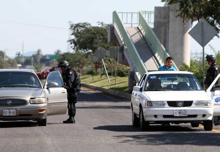 Policías federales custodian las entradas al municipio michoacano de Apatzingán, azotado por la violencia entre autodefensas y cárteles del narcotráfico. (EFE)