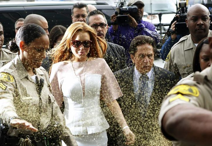 Lindsay Lohan fue recibida al llegar a la corte por una multitud entre las cuales, una desconocida bañó a la actriz con un spray de pintura dorada. (Agencias)