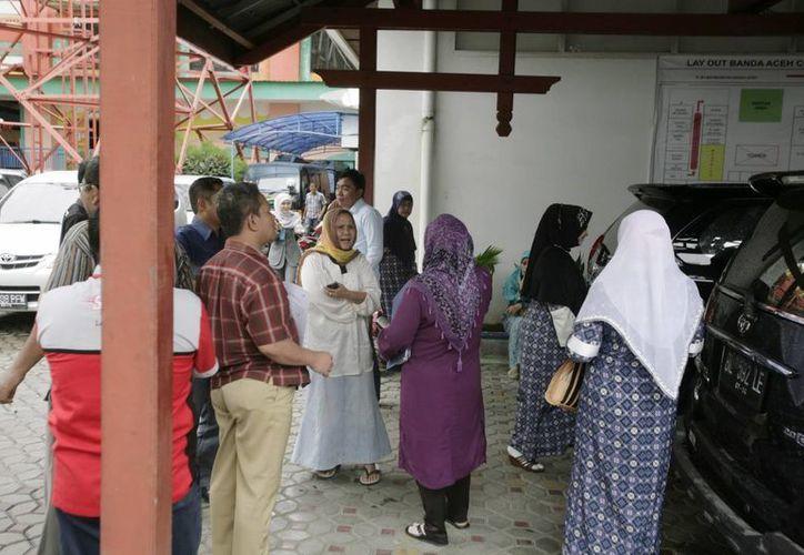 Empleados de una sucursal bancaria en Banda Aceh aguardan en la calle tras el terremoto. (EFE)