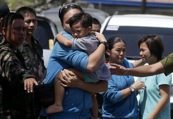 Un niño rescatado por el ejército filipino se reúne con su padre. (Agencias)