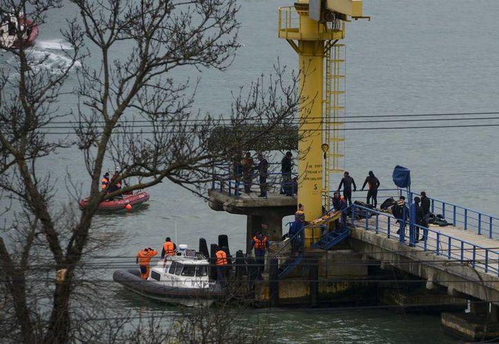 Trabajadores rusos de rescate recogen restos de un avión estrellado en un muelle junto a la localidad de Sochi. (AP/Viktor Klyushin)
