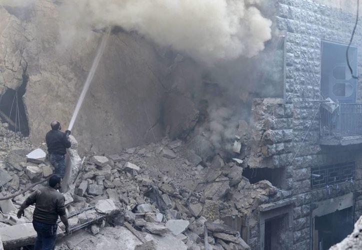 Unos civiles tratan de sofocar un incendio tras un ataque aéreo por parte del régimen sirio en el barrio de Kalase en Alepo, Siria. (Archivo/EFE)
