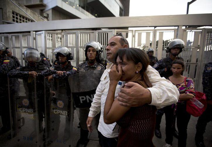 Miembros de la oficinal del encarcelado concejal Alberto Albán Salazar, se abrazan a las afueras de las instalaciones del Servicio Bolivariano de Inteligencia Nacional (SEBIN) en Caracas, Venezuela, (AP)