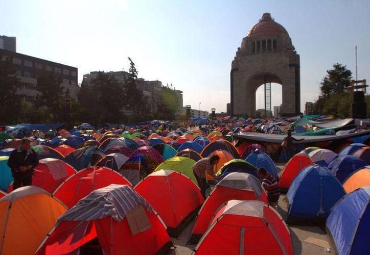 El conflicto magisterial en Oaxaca tien más de 30 años, asegura el gobernador Gabino Cue, quien intenta 'hacerse a un lado' del problema de los profesores. En la imagen,  protesta de profesores en el Monumento a la Revolución, en la ciudad de México. (Archivo/NTX)
