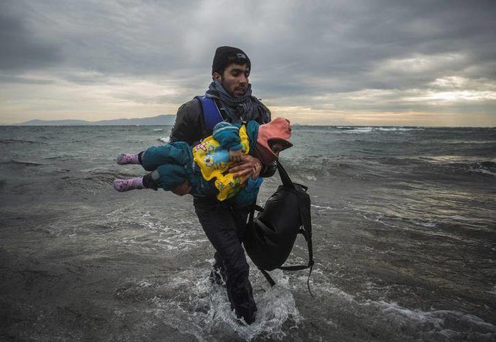 Un hombre carga a un niño mientras tratan de llegar a la costa tras caerse al mar al desembarcar de un bote en el que cruzaron parte del mar Egeo desde Turquía hasta la isla griega de Lesbos. (Agencias)