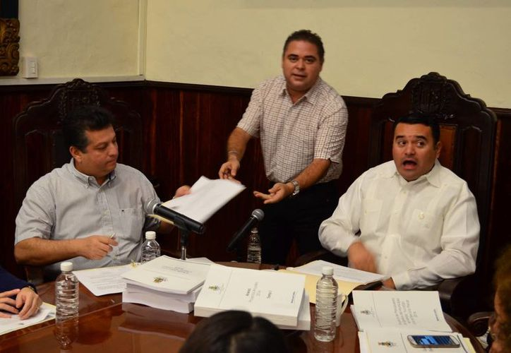 El regidor priista Enrique Alfaro Manzanilla entrega el análisis de la bancada del PRI al secretario del Ayuntamiento, Alejandro Ruz Castro, dado que el alcalde Renán Barrera Concha se negó a recibirlo. (Cortesía)