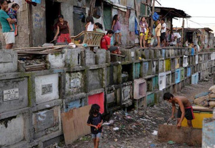 Las personas que viven en el cementerio de Filipinas afrontan muchos retos y desafíos. (actualidad.rt.com)