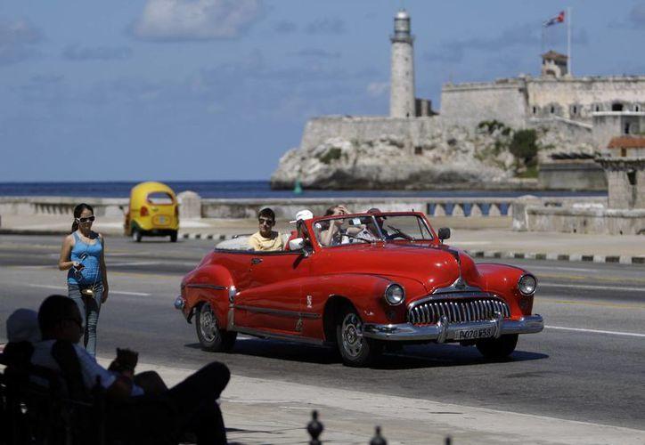 Varios turistas pasean en un vehículo clásico estadounidense por el Malecón de La Habana, Cuba. (Agencias)