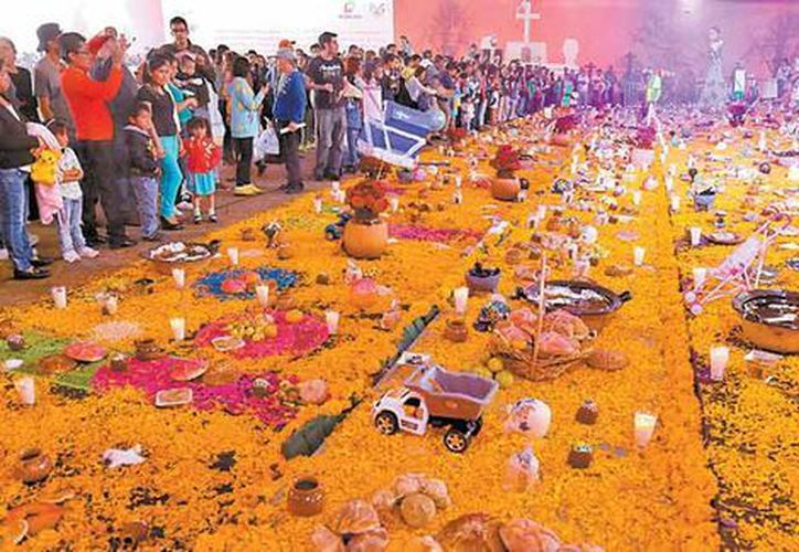 El altar de muertos de 846.48 metros cuadrados instalado en la explanada de la Plaza Juárez de Pachuca, Hidalgo, rompió el récord Guinness. (Milenio).