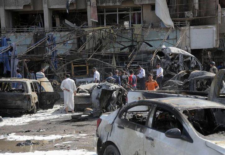 Curiosos inspeccionan la zona en donde 2 vehículos cargados de explosivos estallaron, en Bagdad, Irak. Al menos 8 personas murieron, en otro día más de enfrentamientos entre grupos afines al Gobierno y simpatizanes del Estado Islámico (EI). (AP)
