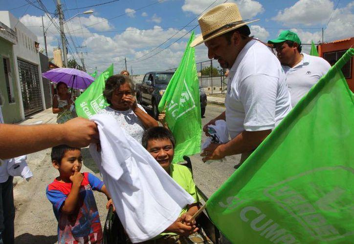 Francisco Torres Rivas, candidato del PRI-PVEM al IV Distrito federal habla con Guadalupe Estrella Pat y uno de sus hijos discapacitados. (SIPSE)