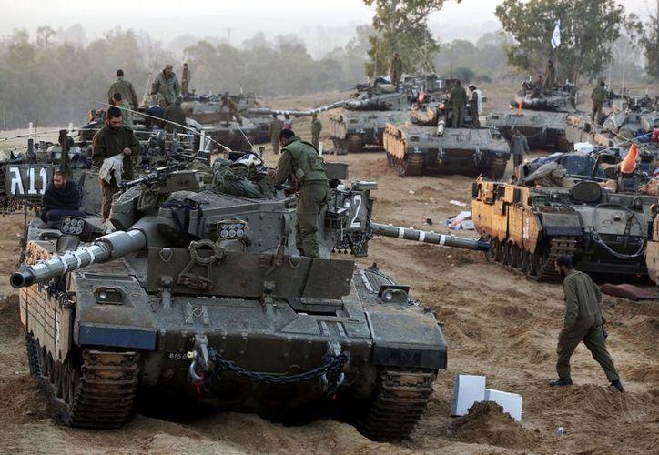Soldados israelís trabajan en un área de estacionamiento cerca de la Franja de Gaza. (Agencias)