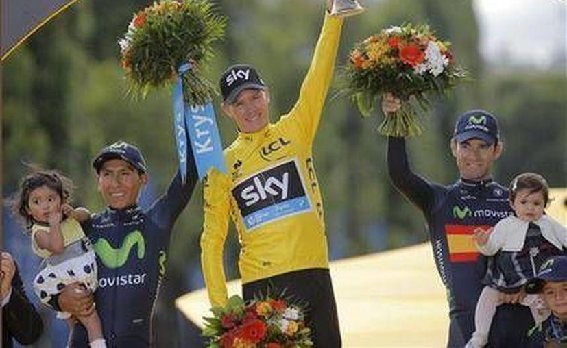 El ciclista inglés Chris Froome (c), del equipo Sky, celebra en la ceremonia de premiación de la Tour de France flanqueado por el colombiano Nairo Quintana (i) y el español Alejandro Valverde (d). Froome y Quintana ya habían compartido el podio, con los mismos puestos, en la edición 2013 de la Tour. (Foto AP)