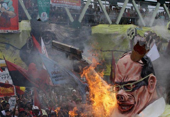 Además de la guerrilla -que cobró la vida de 21 personas- Filipinas tiene que luchar contra las protestas: en la imagen, inconformes queman una efigie del presidente Benigno Aquino, rechazado por su política de programas asistenciales. (AP)
