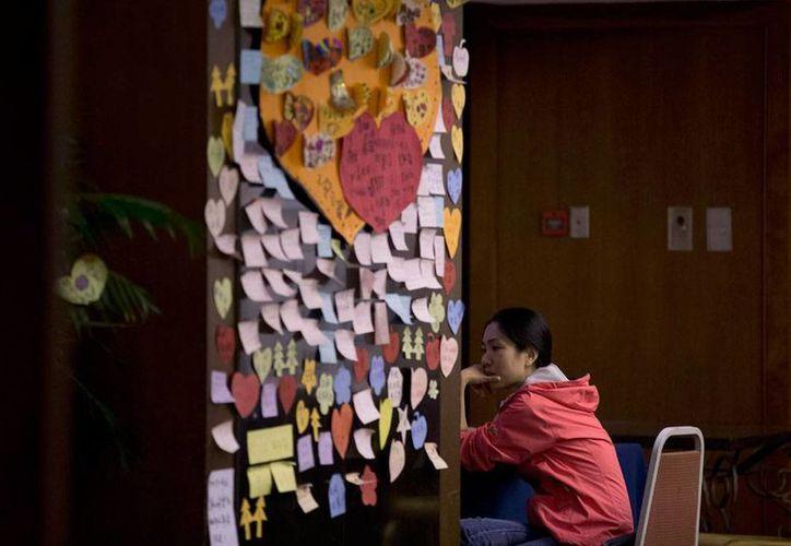 La revelación de que el copiloto del avión de Malaysia Airlines intentó comunicarse tras la desaparición de la aeronave deja más dudas. Imagen de una mujer cerca de una pared con mensajes para los pasajeros, en China. (AP)