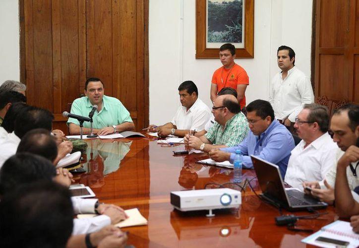 El secretario general de Gobierno, Roberto Rodríguez Asaf (al fondo, al centro), se reunió con el 'grupo de primera respuesta' en torno al monitoreo de un disturbio tropical que ocasionará intensas lluvias. (Foto cortesía del Gobierno de Yucatán)