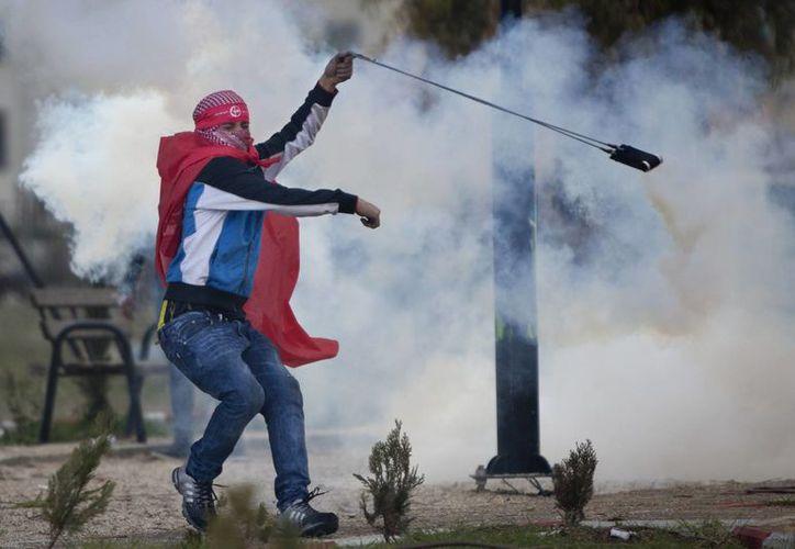 Desde principios de octubre, al menos 114 palestinos han muerto, muchos de ellos abatidos por las fuerzas israelíes. Imagen de un manifestante palestino al utilizar una honda para lanzar de nuevo una granada de gas lacrimógeno contra las tropas israelíes a raíz. (Agencias)