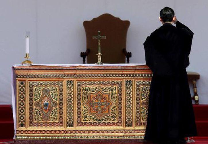 Un sacerdote se santigua en el altar vacío del hospital Policlínico Gemelli de Roma, Italia. (EFE)