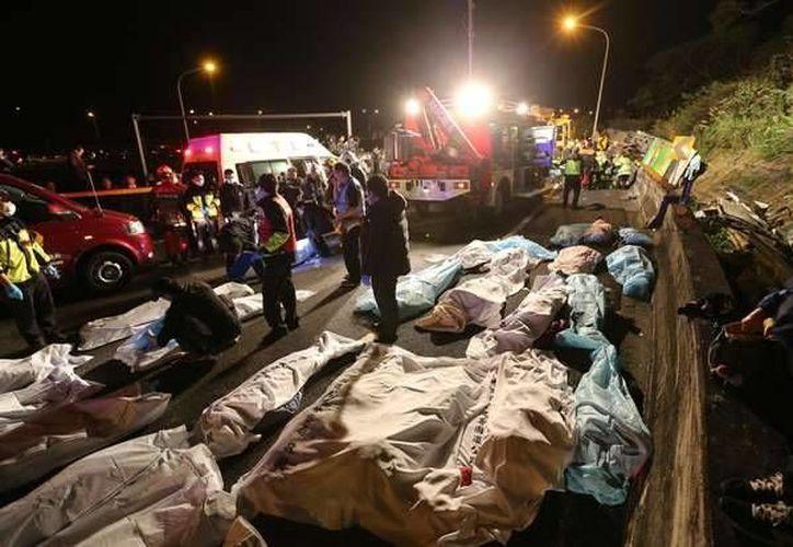 Paramédicos cubren los cuerpos de las víctimas, en el lugar donde se registró la volcadura del autobús, en una autopista de Taipei, Taiwán. (AP Photo)
