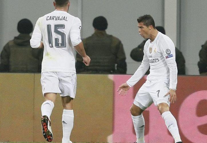 Dani Carvajal se dispone a felicitar a Cristiano Ronaldo por un gol conseguido ante el Shakthar Donetsk ucraniano en partido de la fase de grupos de la Liga de Campeones de Europa. Ronaldo marcó un doblete para contribuir al 4-3 a favor. (EFE)