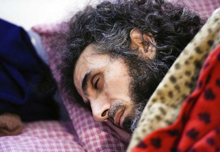 Fotografía del 9 de septiembre del sirio Abu Wa'el Dhiab descansa en la cama tras conversa con su familia a través de una laptop en su apartamento en Montevideo, Uruguay. (AP/Matilde Campodónico)