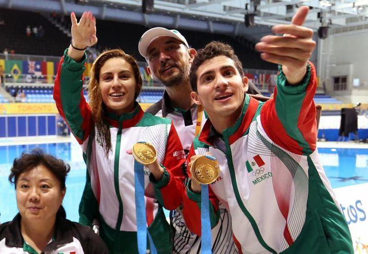 Paola Espinosa (i) y Rommel Pacheco muestran las primeras medallas de oro ganadas por ellos y por México en los Juegos Panamericanos de Toronto. (Fotos: Notimex)
