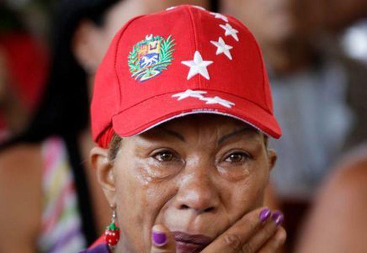 Una seguidora de Hugo Chávez llora a las afueras del hospital militar donde el Presidente de Venezuela se encuentra internado. (Agencias)