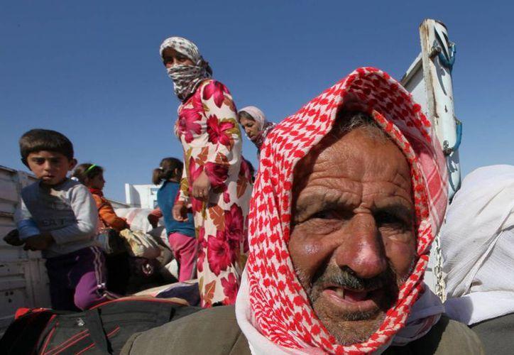 Refugiados kurdos sirios suben a un camión después de su llegada a Turquía al intensificarse los combates entre kurdos sirios y el Estado Islámico en las inmediaciones Kobani, Siria. (Agencias)