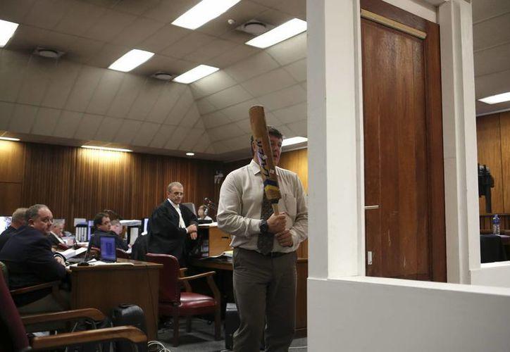 Un policía participa en la reconstrucción de la rotura de la puerta con el bate de crícket durante el juicio contra Pistorius. (EFE)