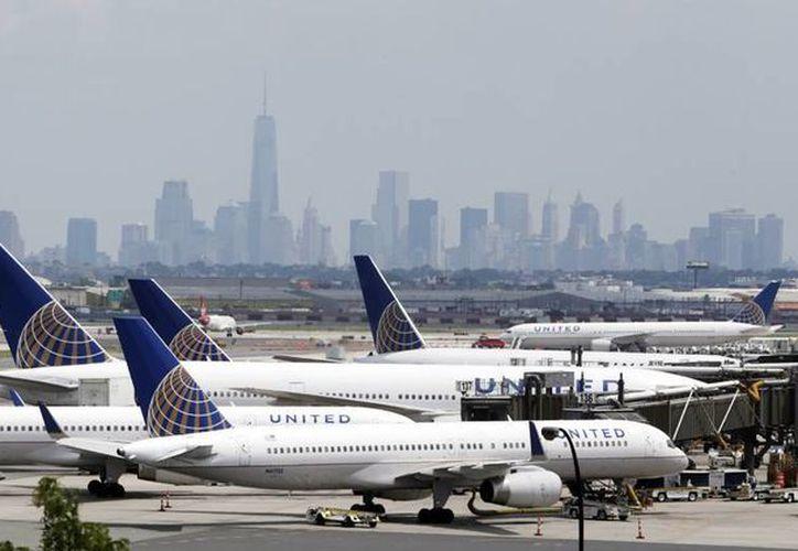 Imagen de un grupo de aviones de la línea aérea United Airlines que están estacionados en la pista del Aeropuerto Internacional Newark Liberty , en Newark, Nueva Jersey. Todos los vuelos están parados por problemas informáticos. (AP Photo/Julio Cortez , Archivo)