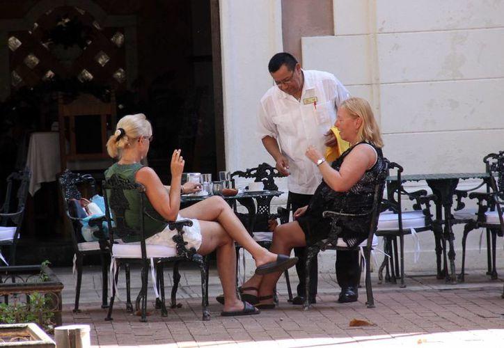 Las perspectivas laborales para el próximo año son favorables. Imagen de un mesero que atiende a dos turistas en el centro de Mérida. (Milenio Novedades)