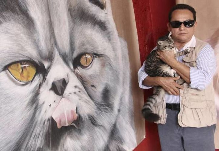 Los lienzos de los gatos miden aproximadamente unos cuatro metros de altura. En la foto, José Luis Loría posa junto a una de sus obras. (Archivo/SIPSE)