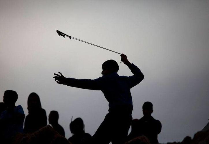 Un palestino utiliza una honda para lanzar una piedra contra soldados de Israel, durante una protesta, en Hebrón. (AP)
