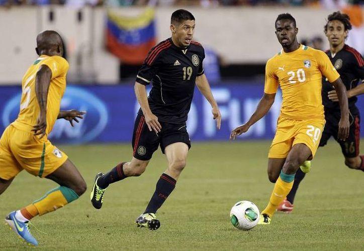 Peralta (c) dribla a Didier Zokora (i) y a Abdul Razak en una jugada del primer tiempo. (Agencias)