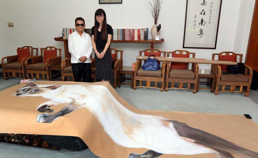 José Luis Loría con una de sus grandes obras que se expone en el Museo de Arte de Guandong. (Milenio Novedades)