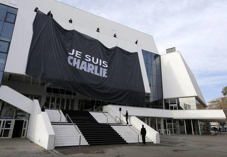 """Trabajadores instalan una pancarta gigante con la leyenda """"Soy Charlie"""" en honor a las víctimas del tiroteo en el periódico satírico Charlie Hebdo, en el Palacio de Festivales de Cannes, en Cannes, sureste de Francia. (Agencias)"""