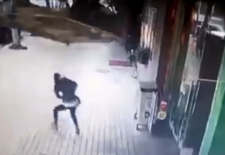 La mujer no logró esquivar el letrero. (Captura video)