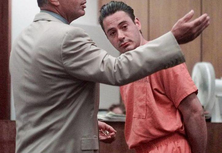 En foto de agosto de 1999, el abogado defensor Robert Shapiro (i) pide que le quiten las esposas al actor Robert Downey Jr. durante una audiencia penal. Hoy el actor  fue indultado por el gobernador de California.  (AP)