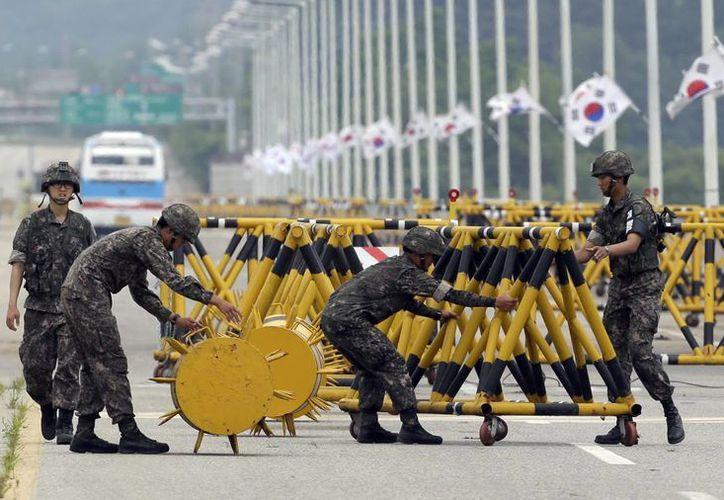 Soldados de Corea del Sur ajustan barricadas cerca de la villa de Panmunjom,  en la zona que separa las dos Coreas. (Agencias)