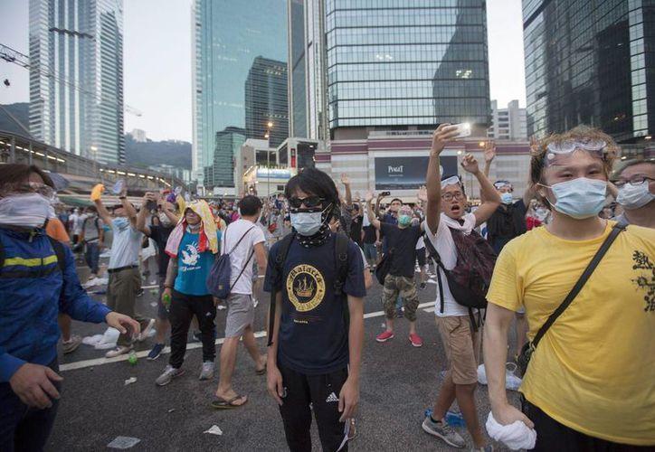 Los manifestantes que protestan en Hong Kong se protegen con máscaras de los gases lanzados por la policía. (EFE)