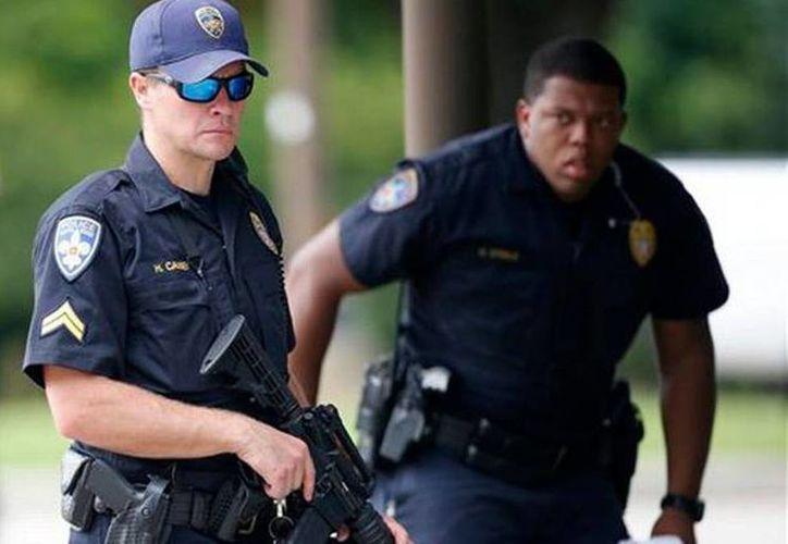 Dos policías vigilan en la entrada a la sala de urgencias del Centro Médico Nuestra Señora del Lago, a donde fueron trasladados policías heridos, en Baton Rouge, Louisiana. Varios agentes policiales fueron muertos o heridos el domingo por la mañana en un tiroteo cerca de una gasolinera en Baton Rouge. (AP Foto/Gerald Herbert)
