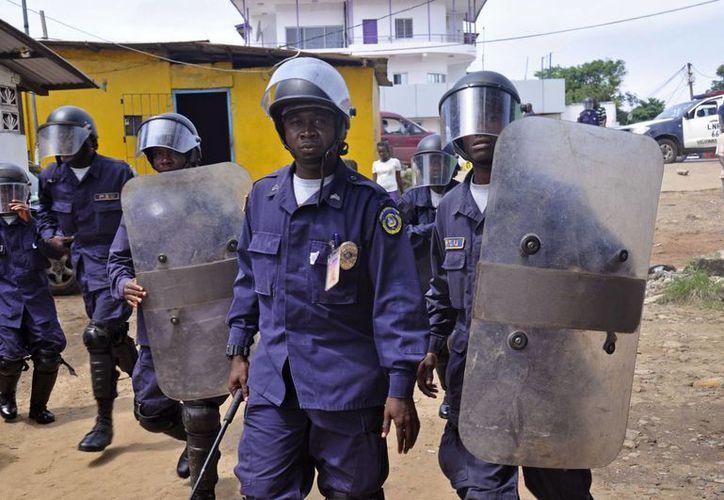 Policías de Liberia dispersan una multitud que bloqueaba una carretera, mientras observan a los trabajadores de salud retirar el cuerpo de un hombre sospechoso de estar contagiado de ébola. (Agencias)