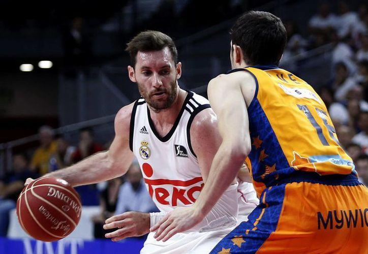 El alero del Real Madrid de basquetbol, Rudy Fernández (i), disputa un balón contra Guillem Vives, del Valencia Basket, durante el primer partido de las semifinales de la Liga de España, ganado por los madrileños en Madrid. (EFE)