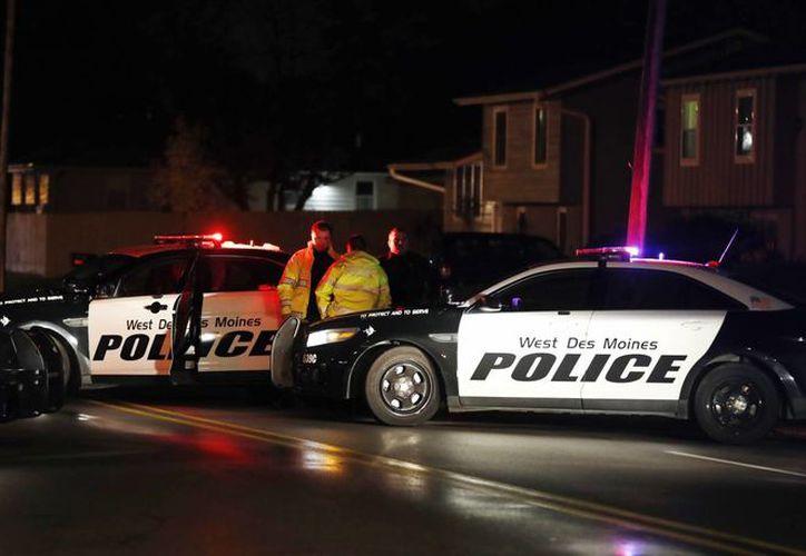 Funcionarios de la policía investigan en la escena de un tiroteo, este miércoles, en Urbandale, Iowa, en donde fallecieron dos policías. (AP foto / Charlie Neibergall)