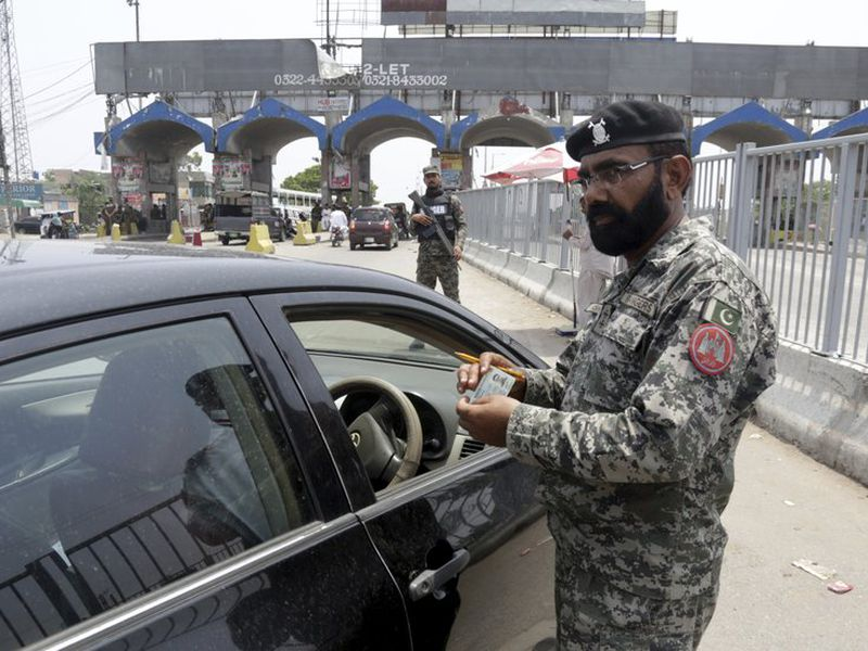 A para military soldier checks identity card of a driver enters in Lahore, Pakistan. (AP)