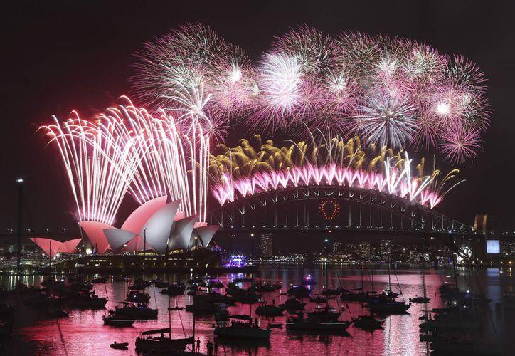 Fuegos artificiales explotan sobre la Casa de la Ópera y el puente de la bahía de Sídney durante la celebración de Año Nuevo en Sídney, Australia, este 31 de diciembre de 2014. (Foto AP/Rob Griffith)