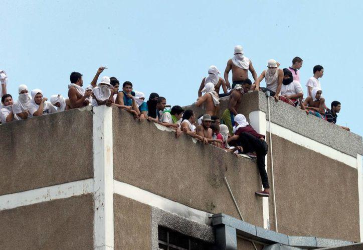 Presos en el techo del centro de detención de la policía bolivariana en Caracas, Venezuela, durante el motín registrado el lunes 27 de abril de 2015. (Foto: AP/Fernando Llano)